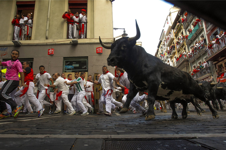 Photo - Dolores Aguirre fighting bulls and revelers run during the running of the bulls of the San Fermin festival, in Pamplona, Spain, Tuesday, July 8, 2014. Revelers from around the world arrive to Pamplona every year to take part on some of the eight days of the running of the bulls glorified by Ernest Hemingway's 1926 novel