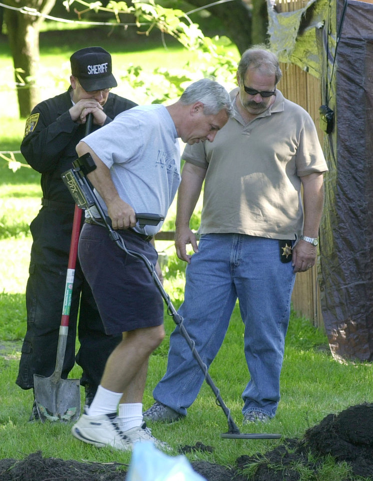 Photo -   FILE - In this July 16, 2003, file photo, Oakland County sheriff investigators search near a backyard pool in Hampton Township, Mich., for evidence linked to the disappearance of ex-teamster boss Jimmy Hoffa. (AP Photo/Carlos Osorio, File)