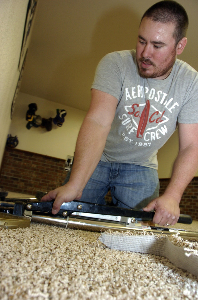 Photo -   Self-employed flooring contractor Chris Folk, 33, installs carpet in a house in Billings, Mont., Friday, Nov. 2, 2012. Folk moved to Billings from Idaho with his wife and two kids when the housing crash dried up work in the Boise area, but he's been unable to sell his Idaho house and is considering declaring bankruptcy. (AP Photo/Matthew Brown)