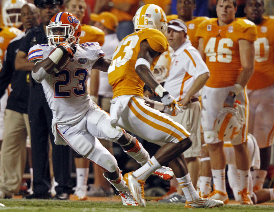Photo -   Florida running back Mike Gillislee (23) runs for yardage as he's defended by Tennessee defensive back Prentiss Waggner (23) in the third quarter of an NCAA college football game on Saturday, Sept. 15, 2012, in Knoxville, Tenn. Florida won 37-20. (AP Photo/Wade Payne)