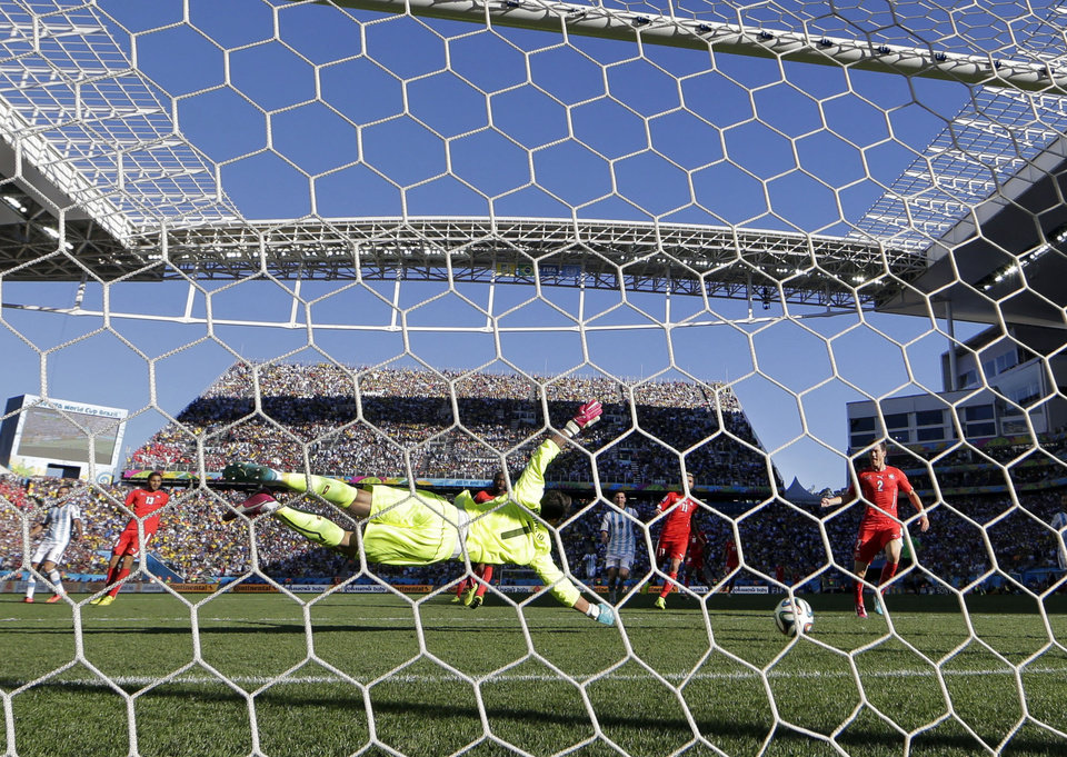 Photo - Switzerland's goalkeeper Diego Benaglio dives but can't stop a goal by Argentina's Angel di Maria in extra time during the World Cup round of 16 soccer match between Argentina and Switzerland at the Itaquerao Stadium in Sao Paulo, Brazil, Tuesday, July 1, 2014. (AP Photo/Victor R. Caivano)