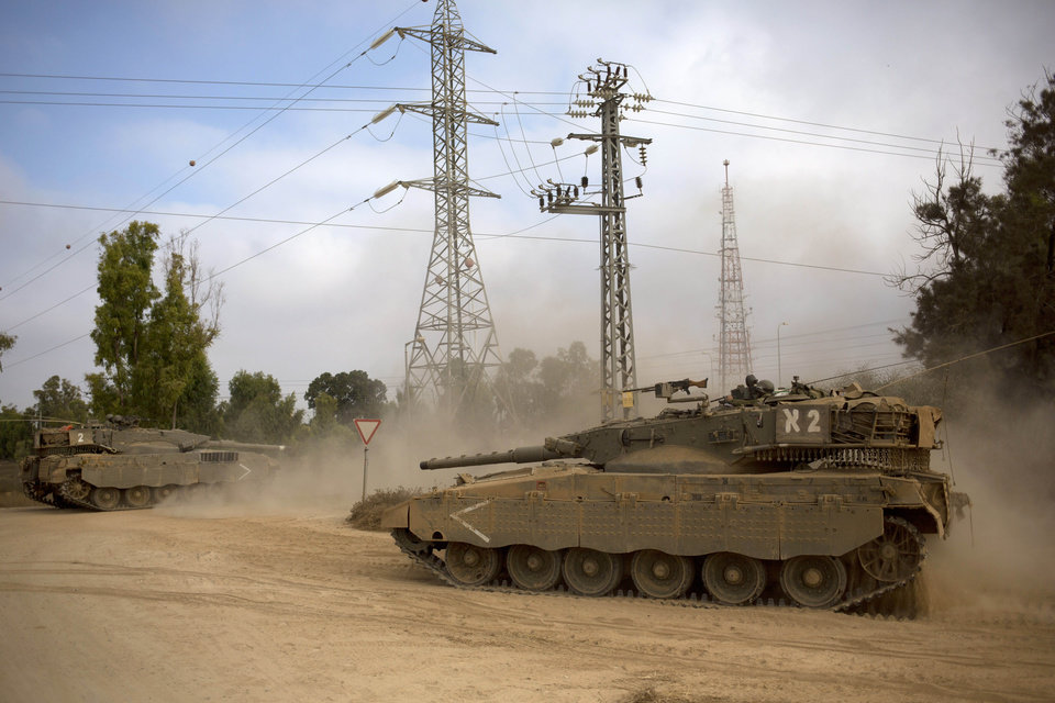 Photo - Israeli tanks move near the Israel and Gaza border Thursday, July 24, 2014. Israeli tanks and warplanes bombarded the Gaza Strip on Thursday, as Hamas militants stuck to their demand for the lifting of an Israeli and Egyptian blockade in the face of U.S. efforts to reach a cease-fire.(AP Photo/Dusan Vranic)