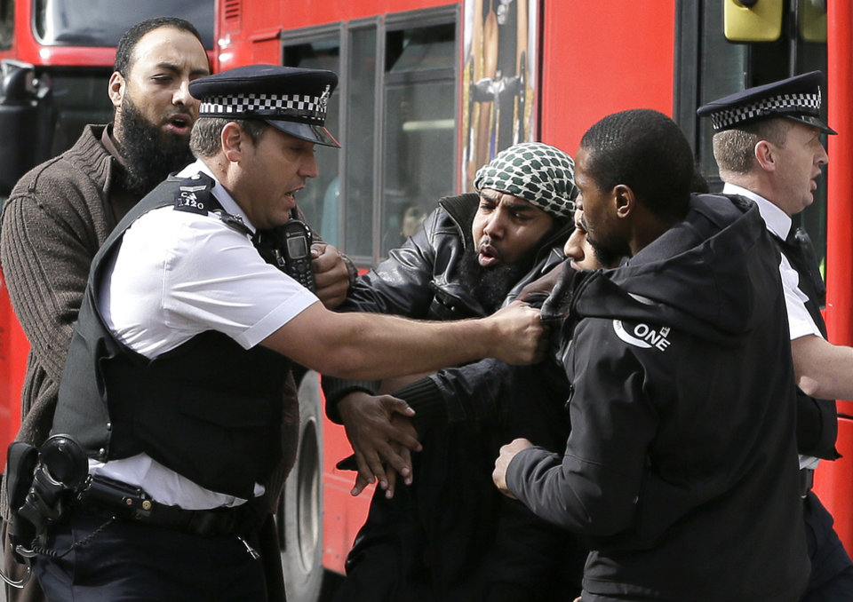 Photo -   Demonstrators clash with police officers outside The Royal Courts of Justice in London Friday, Oct. 5, 2012. Britain's High Court is set to rule Friday afternoon on whether radical cleric Abu Hamza al-Masri and four other terrorist suspects can be extradited to the United States — judgments the government hopes will clear the final hurdle to their removal after years of legal wrangling. (AP Photo/Kirsty Wigglesworth)