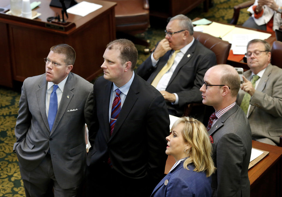 Photo -  Oklahoma Gov. Mary Fallin stands with lawmakers Monday on the House floor to watch votes as they are posted on the tally board at the front of the chamber in Oklahoma City. Standing, from left to right, are: Mike Sanders, Jon Echols, Fallin and Scott Inman. House members voted down raising the cigarette tax rate. [Photo by Jim Beckel, The Oklahoman]