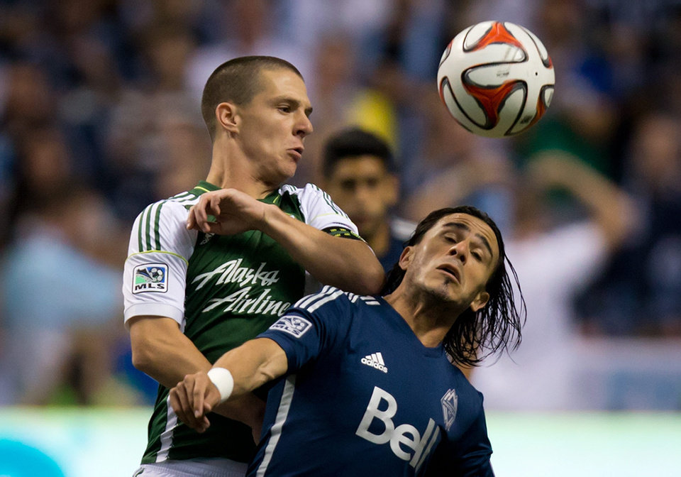 Photo - Portland Timbers' Will Johnson, left, and Vancouver Whitecaps' Mauro Rosales, of Argentina, vie for the ball during the first half of an MLS soccer game in Vancouver, British Columbia, on Saturday, Aug. 30, 2014. (AP Photo/The Canadian Press, Darryl Dyck)