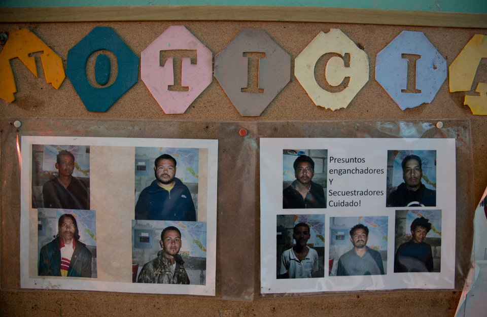 Photo - In this July 10, 2014, photo, pictures of alleged kidnappers, are displayed on a bulletin board in a shelter in Tapachula, Mexico. Smugglers are profiting from the rising violence in gang-ridden cities of Central America, and the yearning of families to be reunited; parents often head north to find work and save money to send for their children, sometimes years later.  (AP Photo/Eduardo Verdugo)