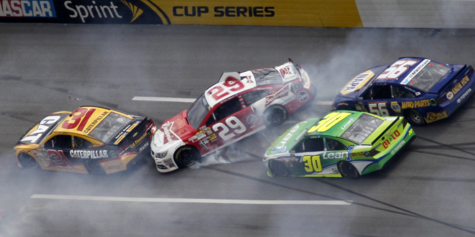 Photo - Cars spin through Turn one in a multi-car wreck during the NASCAR Sprint Cup Series Aaron's 499 auto race at Talladega Superspeedway in Talladega, Ala., Sunday, May 5, 2013. From left: Jeff Burton (31), Kevin Harvick (29), David Stremme (30) and Martin Truex Jr. (AP Photo/Butch Dill)