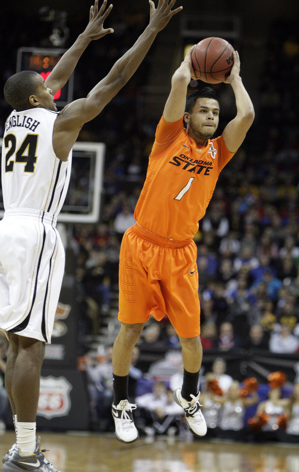 Oklahoma's Cezar Guerrero (1) looks to pass the ball as Missouri's Kim English (24) defends during the Big 12 tournament men's basketball game between the Oklahoma State Cowboys and Missouri Tigers the Sprint Center, Thursday, March 8, 2012.  Photo by Sarah Phipps, The Oklahoman