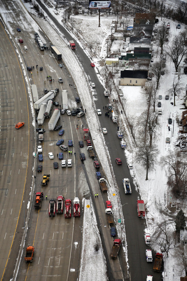 Emergency personnel respond at the scene of one of a mile-long series of crashes along Interstate 75 near the Springwells exit on the southwest side of Detroit Thursday, Jan. 31, 2013. At least three people are dead, including two children, and 20 more were injured in the pileups. (AP Photo/Detroit Free Press, Romain Blanquart)  DETROIT NEWS OUT;  NO SALES