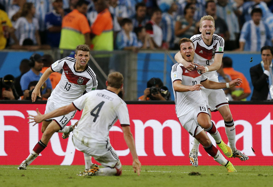 Photo - Germany's Mario Goetze, second right, celebrates with teammates after scoring the lone goal during the World Cup final soccer match between Germany and Argentina at the Maracana Stadium in Rio de Janeiro, Brazil, Sunday, July 13, 2014. Germany beat Argentina 1-0 to win its fourth World Cup title.  (AP Photo/Frank Augstein)