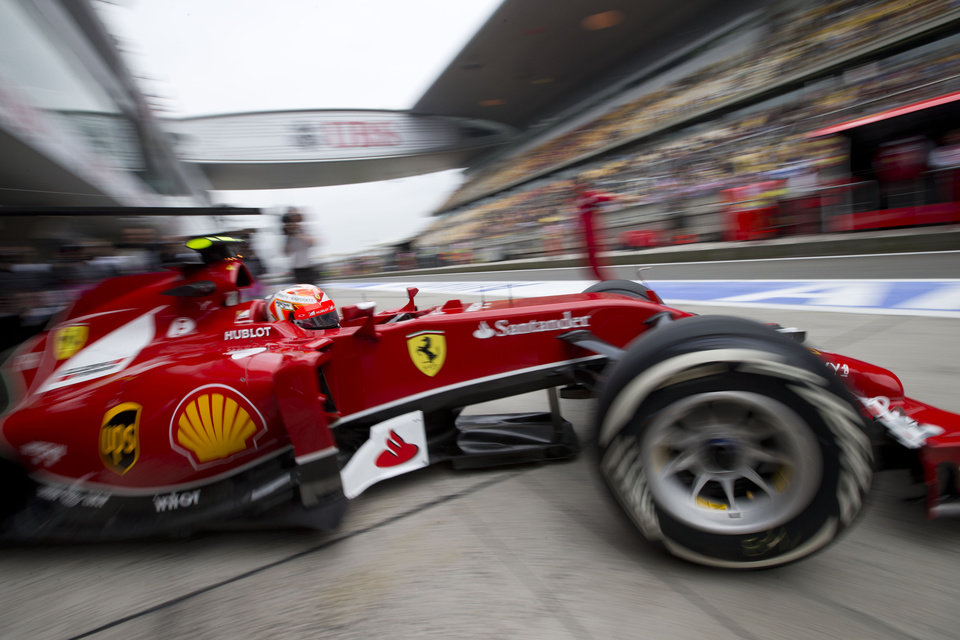 Photo - Ferrari driver Kimi Raikkonen of Finland drives out from the garage during the practice session ahead of Sunday's Chinese Formula One Grand Prix at Shanghai International Circuit in Shanghai, China Friday, April 18, 2014. (AP Photo/Andy Wong)