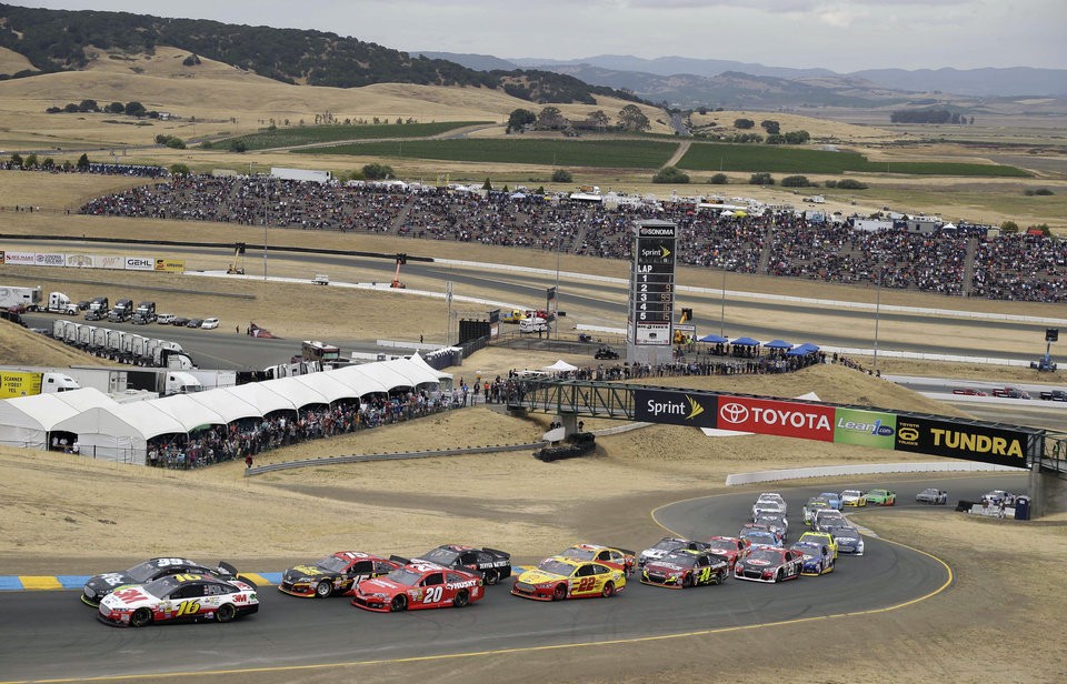 Cars make their way up Turn 2 for the start of the NASCAR Sprint Cup series auto race on Sunday, June 23, 2013, in Sonoma, Calif. (AP Photo/Eric Risberg)