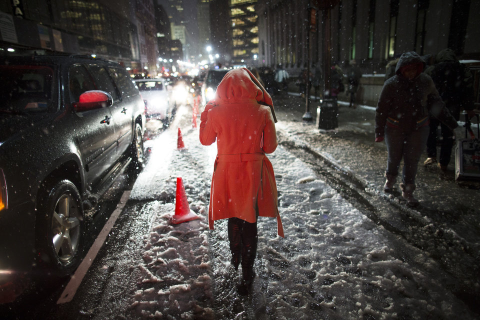 Photo - Snow falls on a pedestrian as she leaves the Rag & Bone Fall 2013 fashion collection show during Fashion Week, Friday, Feb. 8, 2013, in New York. Snow began falling across the Northeast on Friday, ushering in what was predicted to be a huge, possibly historic blizzard and sending residents scurrying to stock up on food and gas up their cars. (AP Photo/John Minchillo)