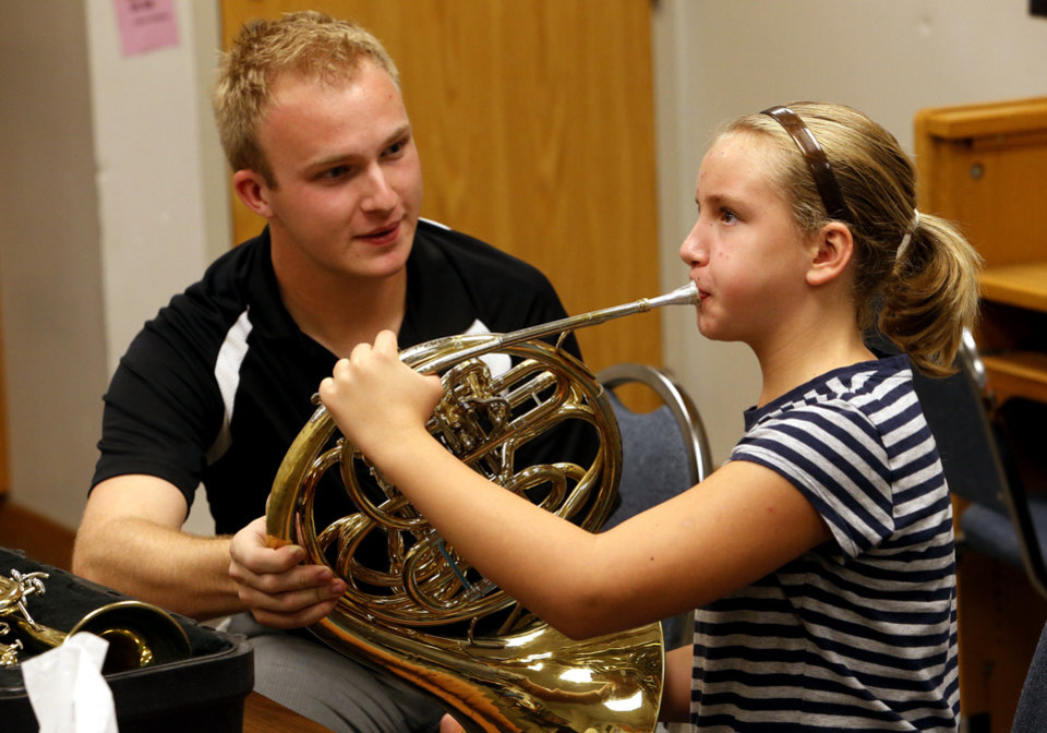 Photo - Matt Hedrick introduces Anwen Wenger to the French horn as middle school students try out band instruments at an instrument fair at Norman High School. Photo by Steve Sisney, The Oklahoman