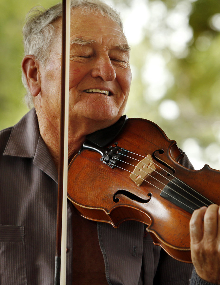 Verlon Stidham plays his fiddle with a jam session at the festival.