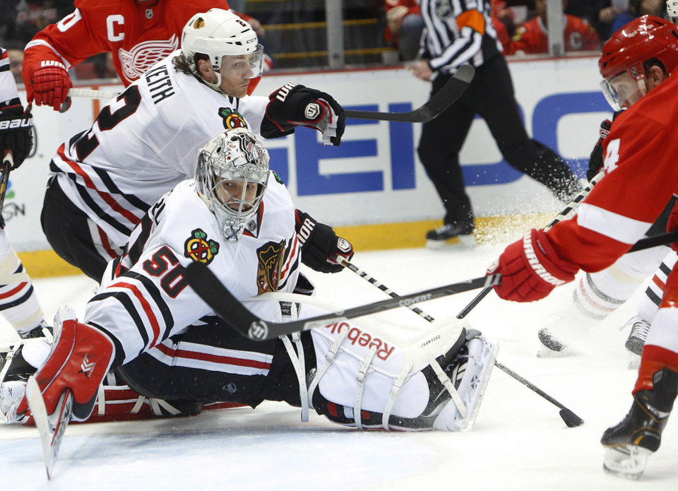 Photo - Detroit Red Wings center Gustav Nyquist, of Sweden, right, scores against Chicago Blackhawks goalie Corey Crawford (50) in the second period of an NHL hockey game Wednesday, Jan. 22, 2014, in Detroit. (AP Photo/Paul Sancya)