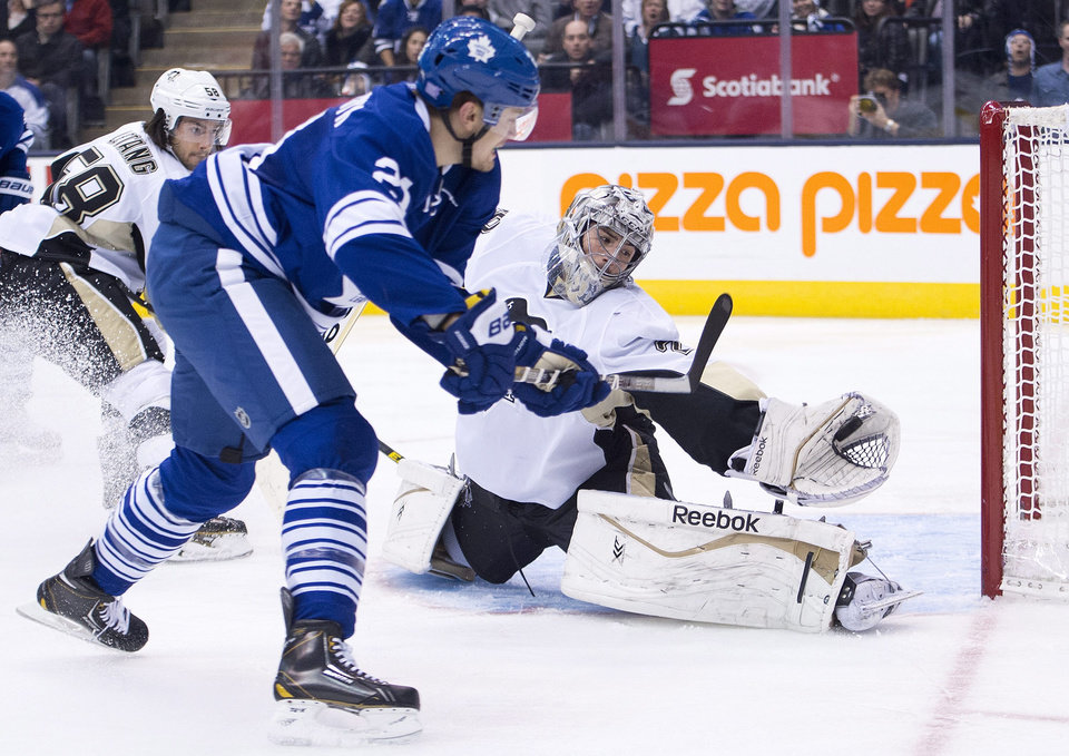 Photo - Toronto Maple Leafs forward James van Riemsdyk, left, gets stoped by Pittsburgh Penguins goalie Marc-Andre Fleury, right, during the second period of an NHL hockey game, Saturday, Oct. 26, 2013 in Toronto. (AP Photo/The Canadian Press, Nathan Denette)