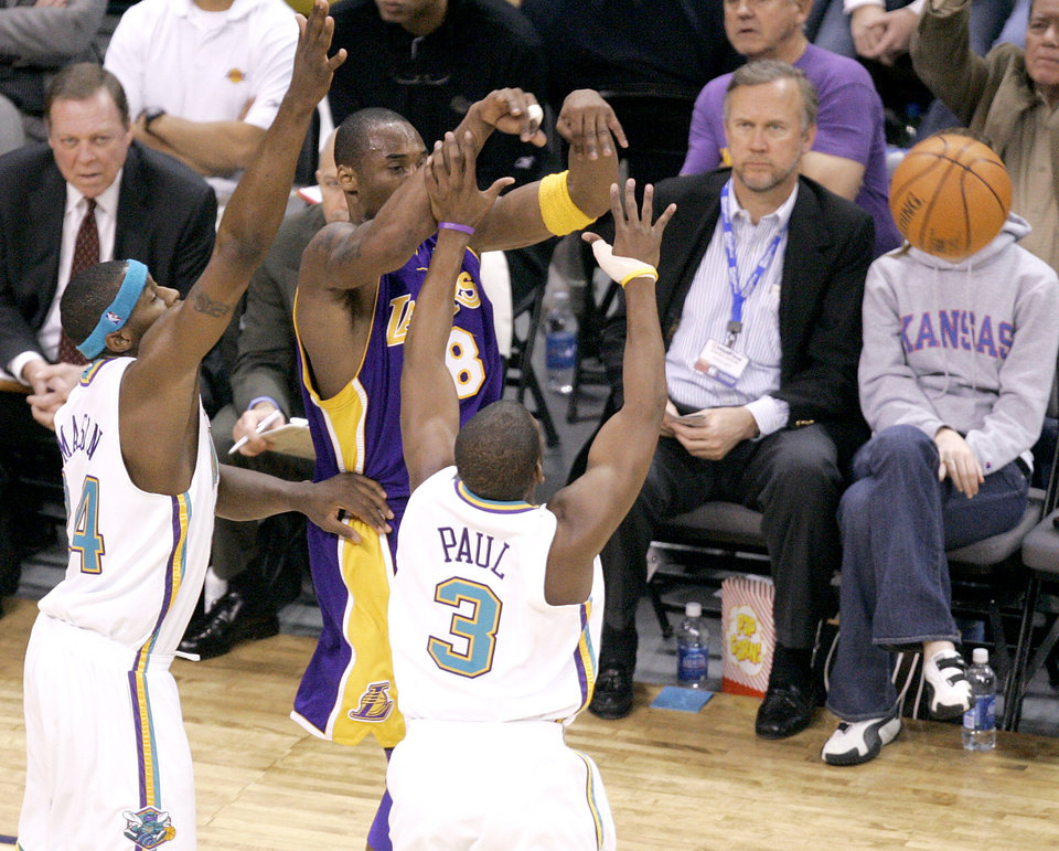Photo - Kobe Bryant of the Lakers passes around Desmond Mason and Chris Paul of the Hornets during the New Orleans/Oklahoma City Hornets NBA basketball game against the Los Angeles Lakers at the Ford Center in Oklahoma City, Feb. 4, 2006.  By Bryan Terry/The Okahoman