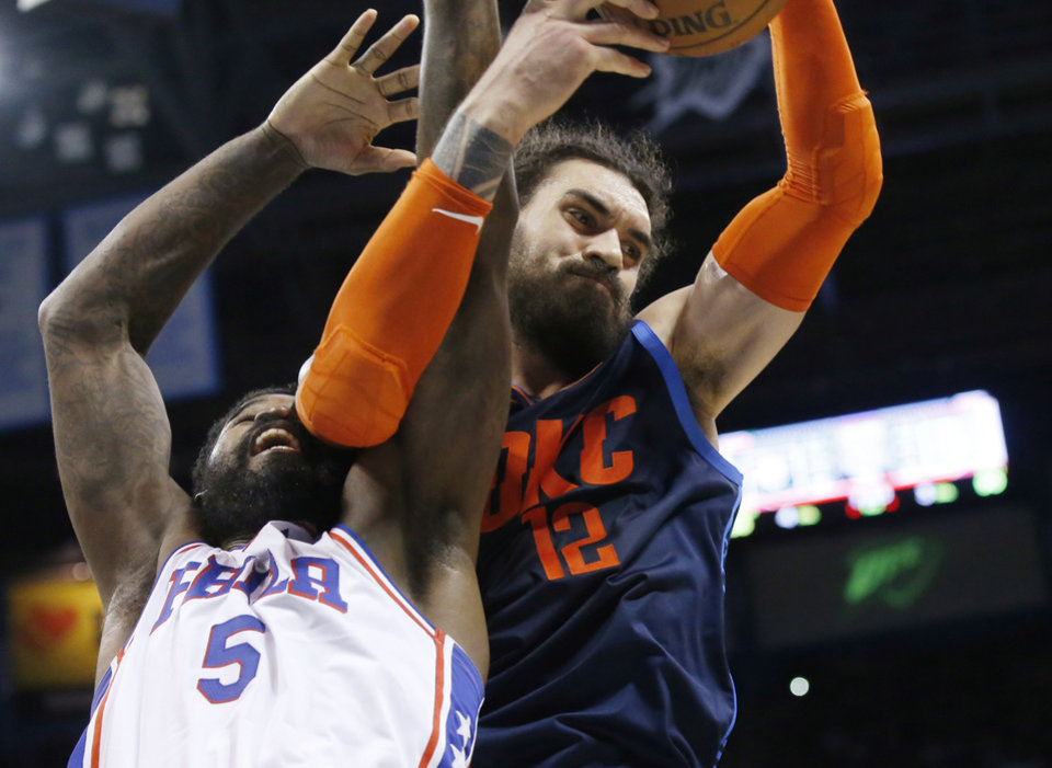 Photo - Oklahoma City Thunder center Steven Adams (12) reaches for a rebound with Philadelphia 76ers center Amir Johnson (5) during the second half of an NBA basketball game Thursday, Feb. 28, 2019, in Oklahoma City. (AP Photo/Sue Ogrocki)