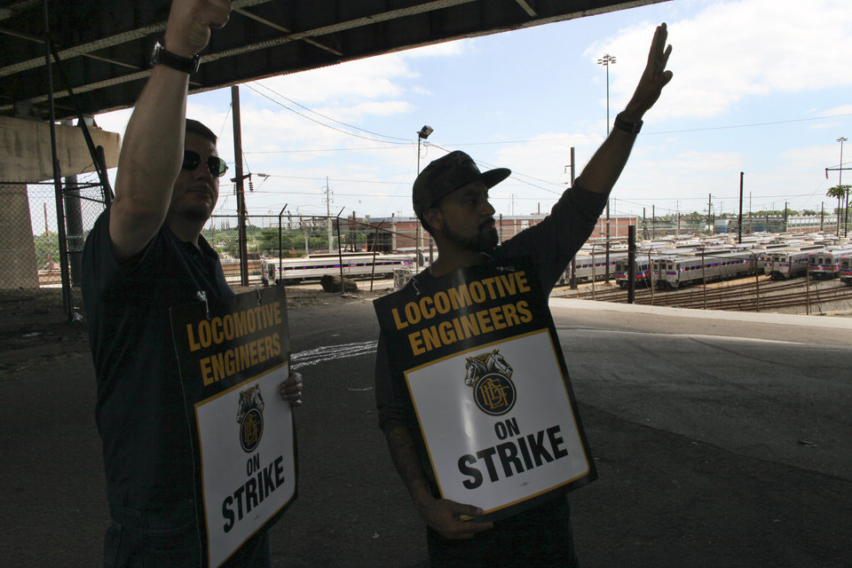 Photo - Two members of the Brotherhood of Locomotive Engineers and Trainmen (BLET) union, who declined to be identified, wave to passing cars as they walk a picket line outside the Roberts Avenue rail yard in Philadelphia on Saturday June 14, 2014, after the two unions went on strike after the two unions went on strike at midnight Friday. Pennsylvania Gov. Tom Corbett asked President Barack Obama on Saturday to intervene the dispute between the Southeast Pennsylvania Transportation Authority and its engineers and electricians unions. (AP Photo/ Joseph Kaczmarek)