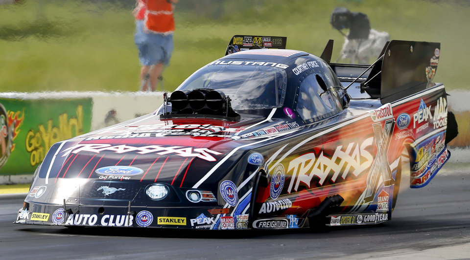 Photo - Funny Car driver Courtney Force floors the throttle on Sunday, May 25, 2014, to defeat Cruz Pedregon in the championship round during the NHRA Kansas Nationals auto race at Heartland Park in Topeka, Kan. Force's run game NHRA women their 100th professional win in the NHRA. (AP Photo/The Topeka Capital Journal, Chris Neal)