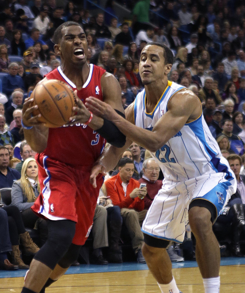 Los Angeles Clippers guard Chris Paul, left, is fouled as he drives to the basket against New Orleans Hornets guard Brian Roberts (22) in the first half of an NBA basketball game in New Orleans, Wednesday, March 27, 2013. (AP Photo/Gerald Herbert)