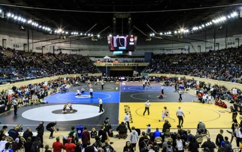Photo -  Wrestlers take to the mats for their matches during the Oklahoma high school state wrestling championships at Oklahoma City's Jim Norick Arena in February 2019. [Chris Landsberger/The Oklahoman]