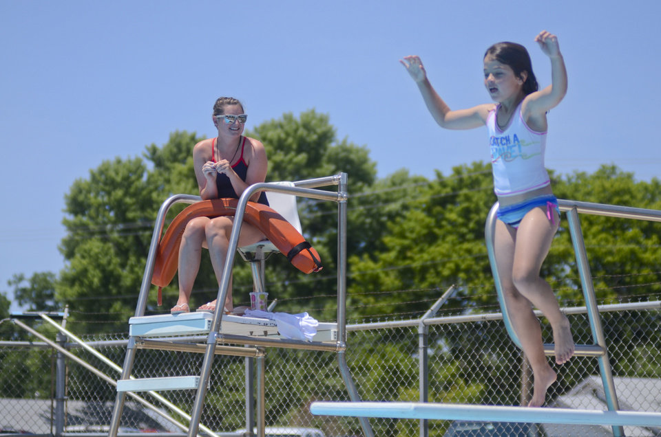 Photo - Lifeguard Darci Thomas, 20, watches as a child makes her way off the diving board at the Stillwater Municipal Pool. PHOTO BY ADAM KEMP, THE OKLAHOMAN