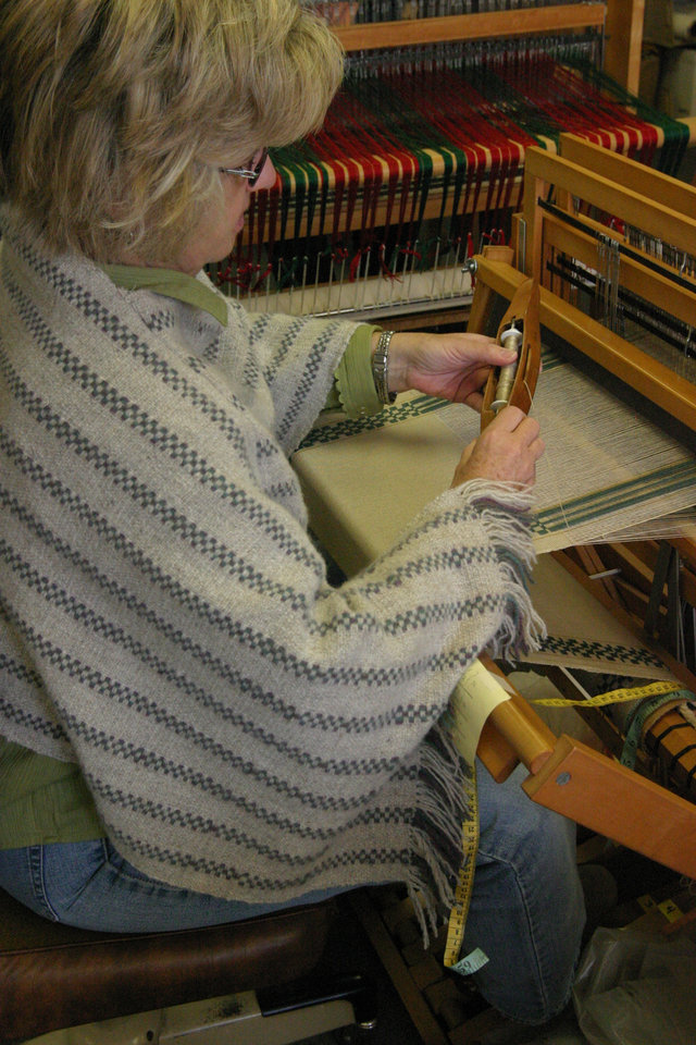 Wearing a poncho she wove, Leslie Sitton is weaving a table runner<br/><b>Community Photo By:</b> Bob Bozarth<br/><b>Submitted By:</b> Sue, Guthrie