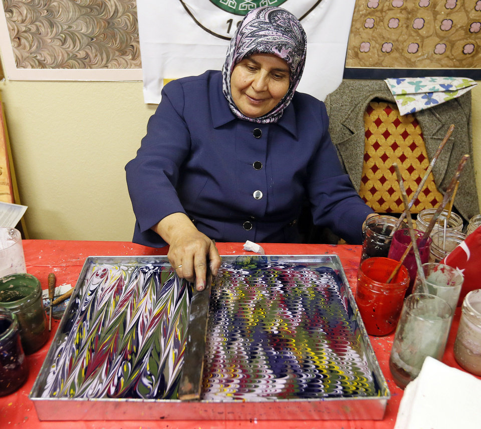 Artist Nuran Oner creates ebru, also  known as paper marbling, during the Turkish  Festival.  Photos by  Nate Billings,  The Oklahoman