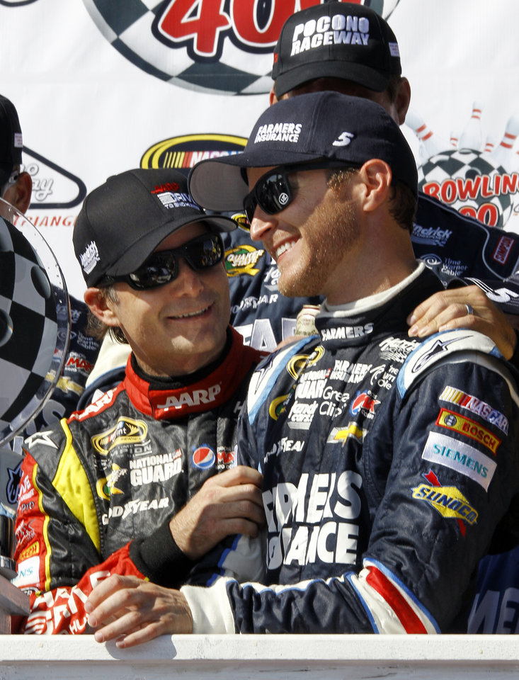 Photo - Jeff Gordon, left, congratulates Kasey Kahne on winning, as they celebrate in victory lane after a NASCAR Sprint Cup Series auto race, Sunday Aug. 4, 2013, at Pocono Raceway in Long Pond, Pa. Jeff Gordon was second. (AP Russ Hamilton Sr.)