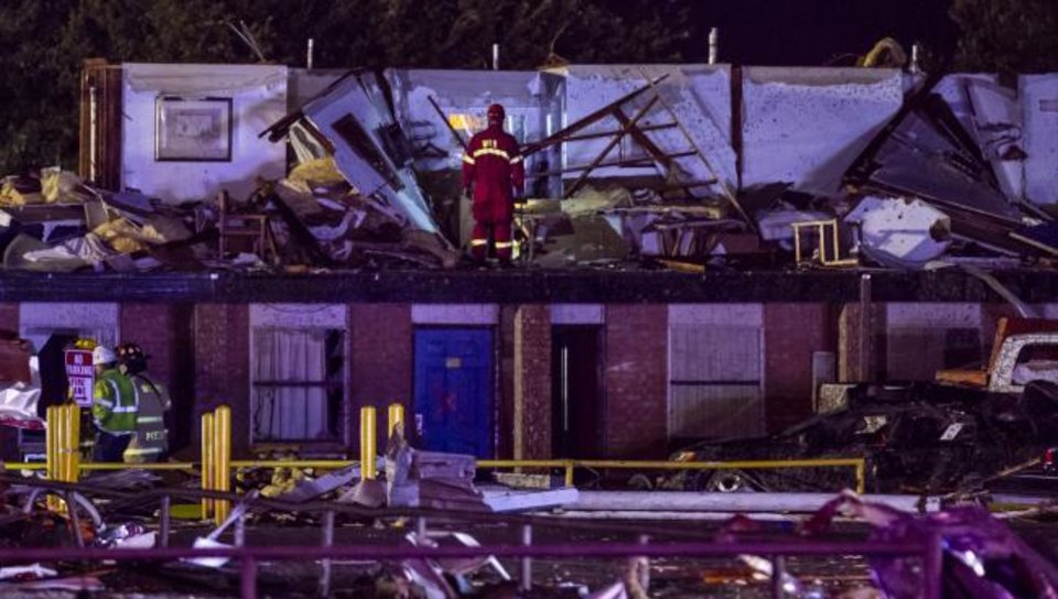 Photo -  Firefighters survey damage at the American Budget Value Inn late Saturday in El Reno. [Chris Landsberger/The Oklahoman]