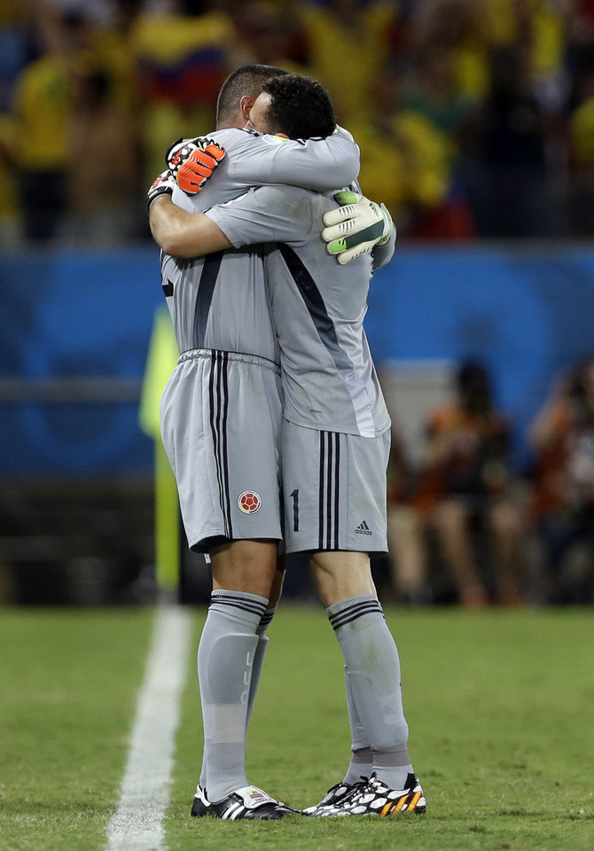 Photo - Colombia's goalkeeper Faryd Mondragon, left, embraces Colombia's goalkeeper David Ospina as he replaces him during the group C World Cup soccer match between Japan and Colombia at the Arena Pantanal in Cuiaba, Brazil, Tuesday, June 24, 2014. (AP Photo/Kirsty Wigglesworth)