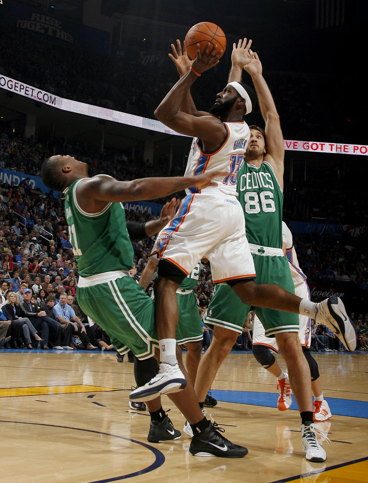 Photo - Oklahoma City's James Harden (13) shoots in between Boston's Glen Davis  (11) and Semih Erden (86) during the NBA game between the Oklahoma City Thunder and the Boston Celtics, Sunday, Nov. 7, 2010, at the Oklahoma City Arena. Photo by Sarah Phipps, The Oklahoman
