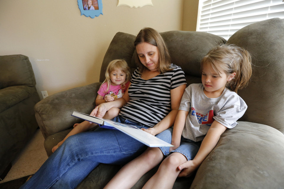 Photo - Haley Argyle looks at an audio book with her daughters Sadie, 3, and Riley, 6, at their home June 6 in Norman. Argyle's husband is deployed with the National Guard and recorded himself reading the audio book for his daughters before he left in February. Photo By Steve Gooch, The Oklahoman  Steve Gooch - The Oklahoman