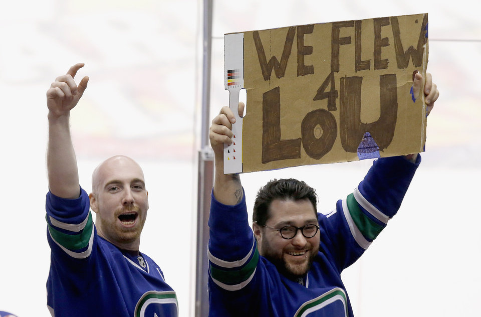Photo - Vancouver Canucks fans make the best of it after learning goalie Roberto Luongo had been traded, as they stand up with a makeshift sign during the third period of an NHL hockey game against the Phoenix Coyotes on Tuesday, March 4, 2014, in Glendale, Ariz.  The Coyotes defeated the Canucks 1-0.(AP Photo/Ross D. Franklin)