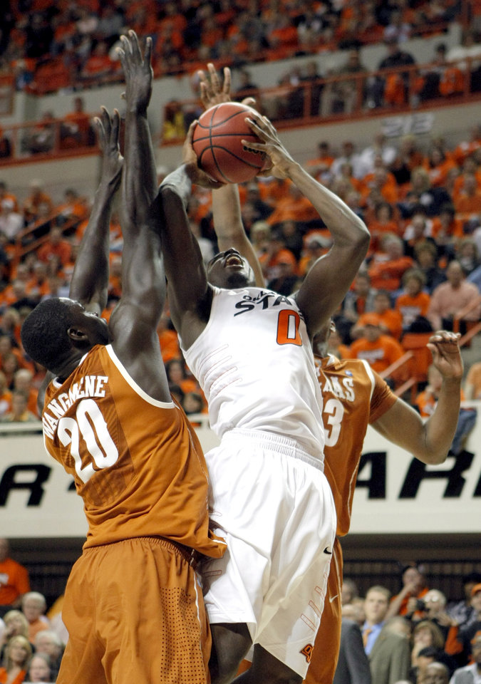 Photo - Oklahoma State's Jean-Paul Olukemi (0) shoots in between Texas' Alexis Wangmene (20) and Texas' Tristan Thompson (13) during the basketball game between Oklahoma State and Texas, Wednesday, Jan. 26, 2011, at Gallagher-Iba Arena in Stillwater, Okla. Photo by Sarah Phipps, The Oklahoman ORG XMIT: KOD