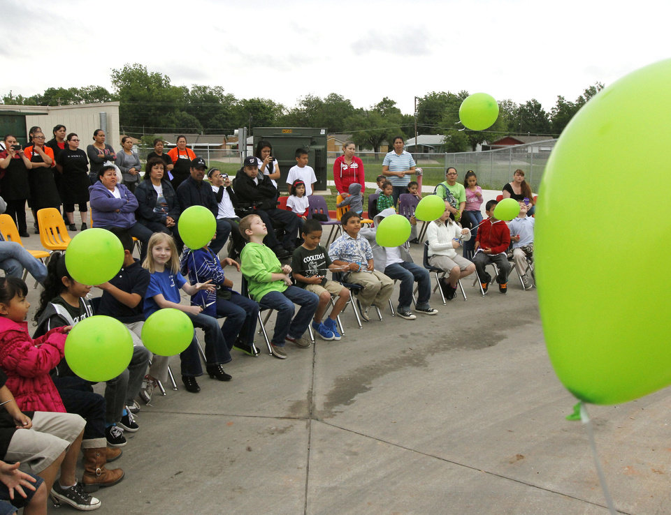 Photo - First-graders release green balloons during a tree-planting ceremony Friday to honor first-grader Roberto Avalos at Coolidge Elementary School. Students said green was Avalos' favorite color. Photo by Paul Hellstern, The Oklahoman  PAUL HELLSTERN - Oklahoman