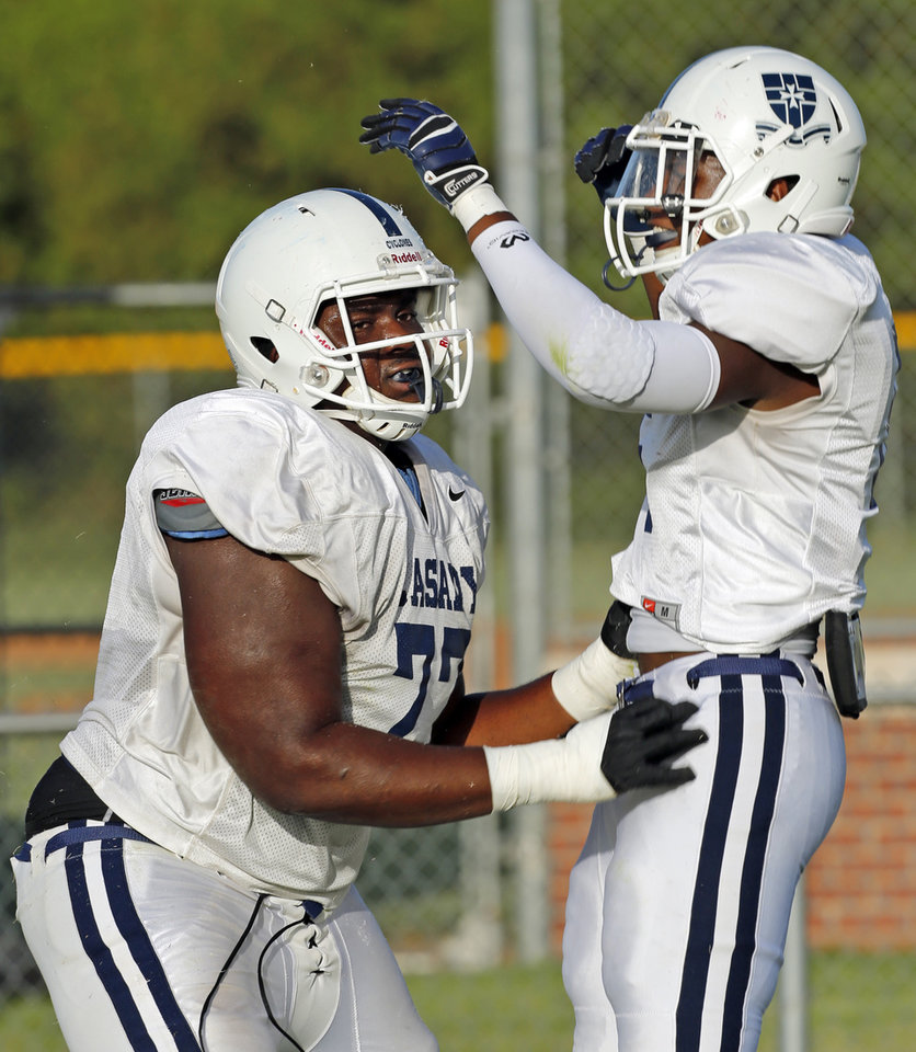 Photo - Casady's Josh Wariboko-Alali celebrates a touchdown with Gary Woods as they play against Christian Heritage Academy during at a high school football scrimmage at Casady School in Oklahoma City, Okla., on Friday, Aug. 22, 2014. Photo by Steve Sisney, The Oklahoman
