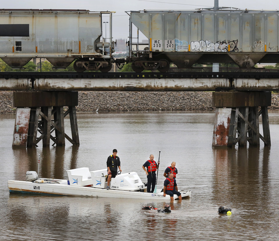 Photo -  Oklahoma City Fire Department divers assisted in locating and removing a truck from the Oklahoma River Thursday afternoon. A person at the Chesapeake Boathouse reported seeing the vehicle roll down a ramp into the water under the Byers Avenue bridge near SE 6. No one was inside the truck. Photo by Jim Beckel, The Oklahoman   Jim Beckel -