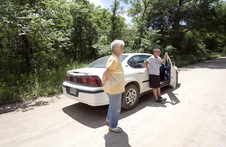 Photo - Anna Roberts and her grandson, Kaleb, 12, on Henryetta, Okla., look at a make-shift memorial on the side of the road, Sunday, June, 14, 2008, near the spot Taylor Paschal-Placker and Skyla Whitaker were shot last week. SARAH PHIPPS, THE OKLAHOMAN