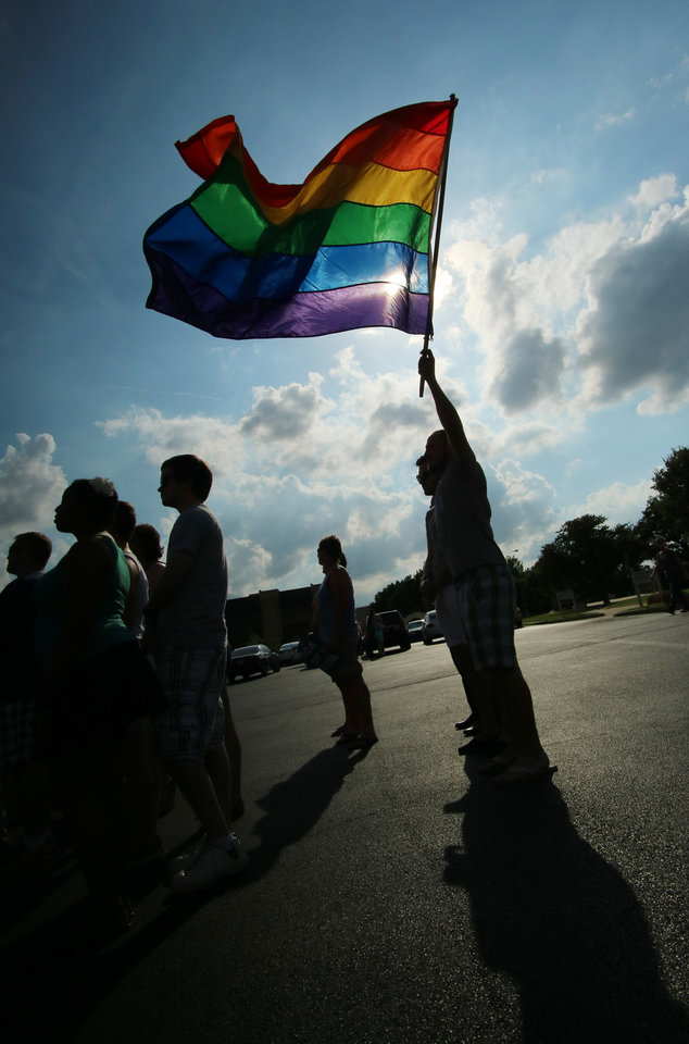 Photo -  Corey Kehn waves the Gay Pride flag with his partner Benjamin Ault during the marriage equality victory rally at Freedom Oklahoma parking lot, Friday, June 26, 2015. Photo by Doug Hoke, The Oklahoman