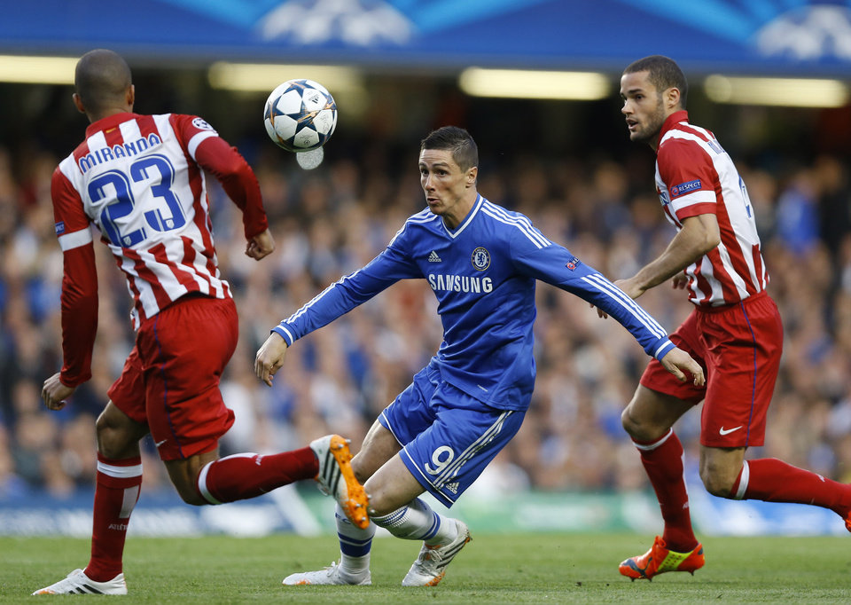 Photo - FILE - In this file photo dated Wednesday, April 30, 2014, Chelsea's Fernando Torres, centre tries to get past Atletico's Miranda, left during the Champions League semifinal second leg soccer match between Chelsea and Atletico Madrid at Stamford Bridge Stadium in London. According to an announcement released by Chelsea soccer club Friday Aug. 29, 2014, Italian club AC Milan have agreed terms for a two-year loan deal for striker Fernando Torres. (AP Photo/Kirsty Wigglesworth FILE)