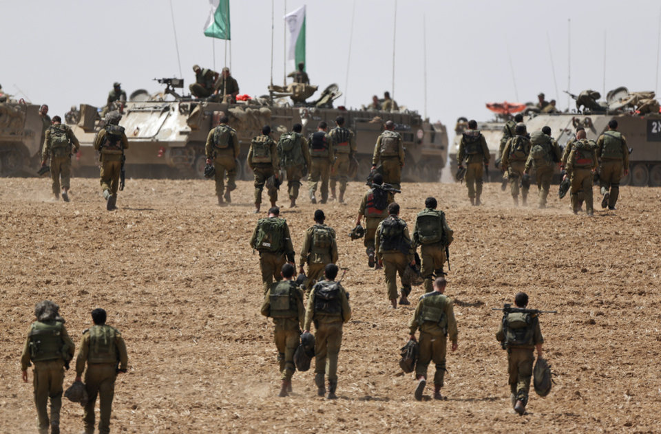 Photo - Israeli infantry soldiers walk to their armored personnel carriers to take up new positions on the Israel-Gaza border, Saturday, July 12, 2014. Israeli airstrikes overnight targeting Hamas in Gaza hit a mosque its military says concealed the militant group's weapons, in an offensive that showed no signs of slowing down. Israel launched its campaign five days ago to stop relentless rocket fire on its citizens. While there have been no fatalities in Israel, Palestinian officials said overnight attacks raised the death toll there to over 120, with more than 920 wounded. (AP Photo/Lefteris Pitarakis)