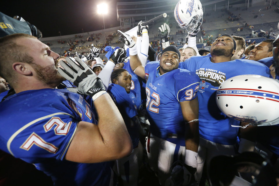 Photo - Tulsa offensive tackle Jared Grigg (72) leads his teammates in celebrating a 31-17 win over Iowa State in the Liberty Bowl NCAA college football game in Memphis, Tenn., Monday, Dec. 31, 2012. (AP Photo/Rogelio V. Solis)
