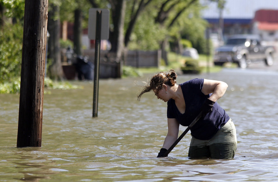 Photo - Molly Brent tries to unclog a sewer drain on a flooded street on Wednesday, April 27, 2011, in West Memphis, Ark. Strong storms hit the South Wednesday for the second straight day. (AP Photo/Mark Humphrey)