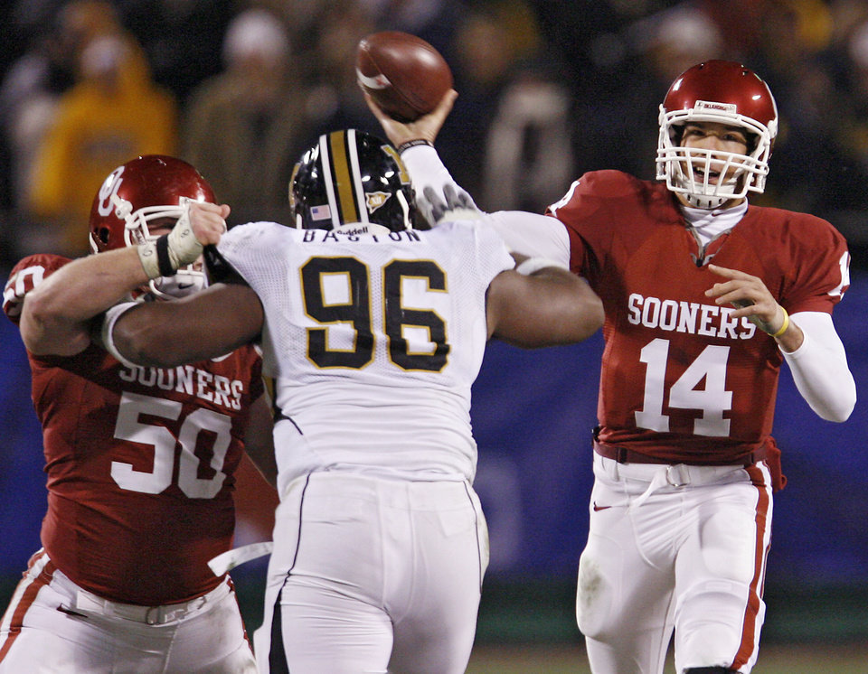 Photo - Oklahoma's Sam Bradford (14) throws the ball against the Missouri defense during the first half of the Big 12 Championship college football game between the University of Oklahoma Sooners (OU) and the University of Missouri Tigers (MU) on Saturday, Dec. 6, 2008, at Arrowhead Stadium in Kansas City, Mo. 