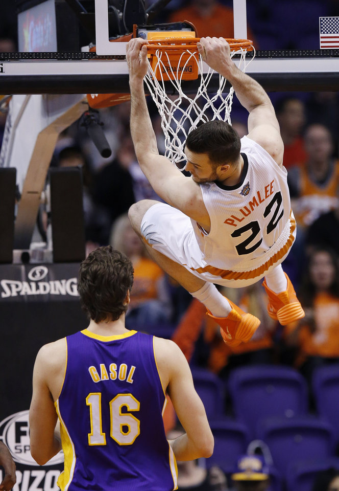 Photo - Phoenix Suns' Miles Plumlee (22) hangs from the rim after dunking as Los Angeles Lakers' Pau Gasol (16), of Spain, watches during the first half of an NBA basketball game Wednesday, Jan. 15, 2014, in Phoenix. (AP Photo/Ross D. Franklin)