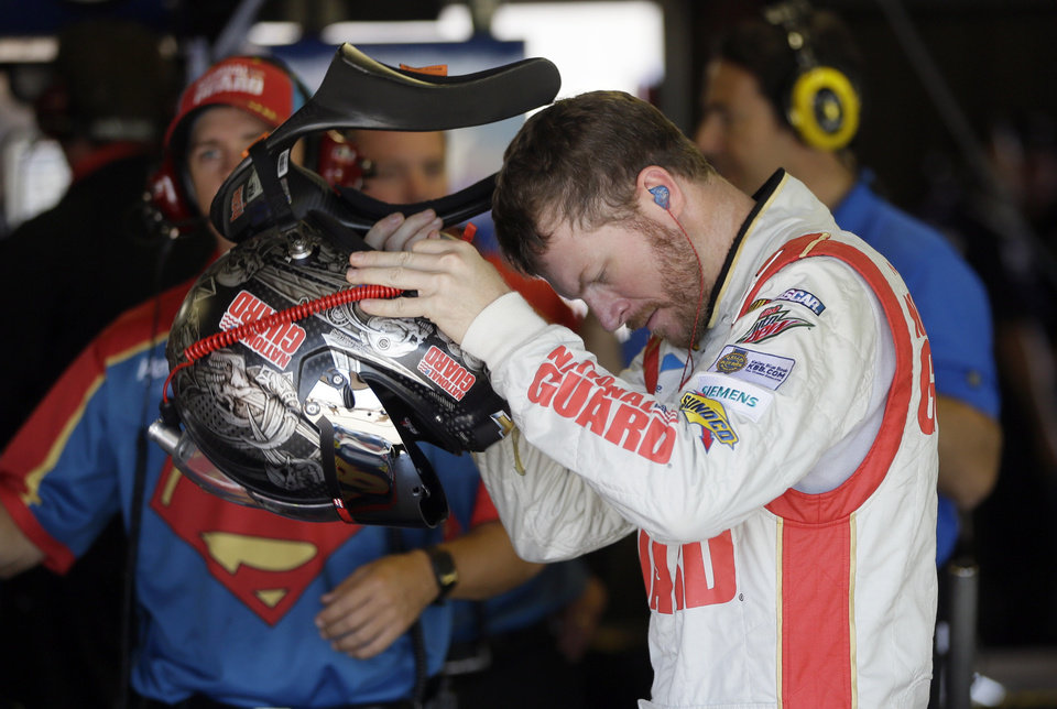 Photo - Driver Dale Earnhardt Jr., prepares for his qualifying session for the NASCAR Sprint Cup series auto race at Michigan International Speedway in Brooklyn, Mich., Saturday, June 14, 2014. (AP Photo/Carlos Osorio)