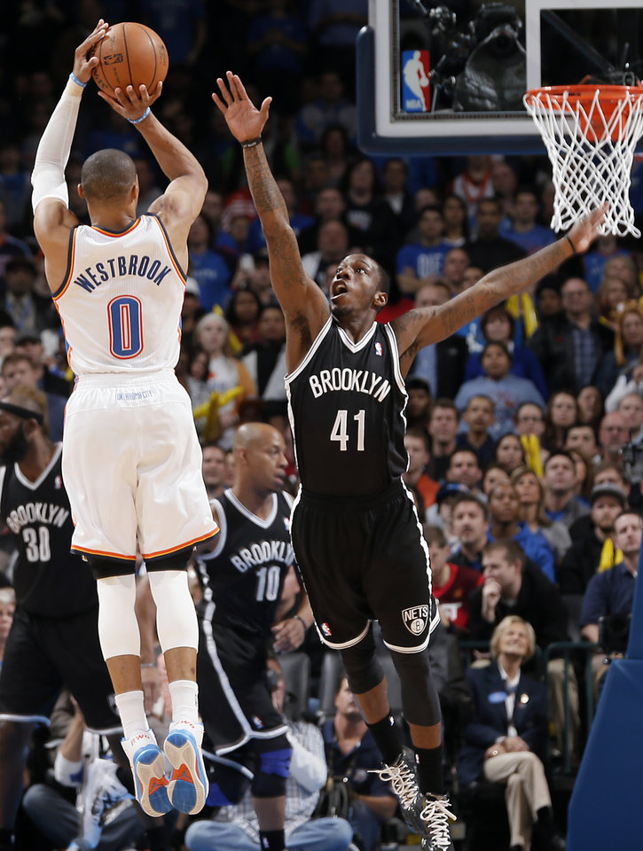 Photo - Brooklyn Nets' Tyshawn Taylor (41) defends on Oklahoma City's Russell Westbrook (0) during the NBA basketball game between the Oklahoma City Thunder and the Brooklyn Nets at the Chesapeake Energy Arena on Wednesday, Jan. 2, 2013, in Oklahoma City, Okla. Photo by Chris Landsberger, The Oklahoman